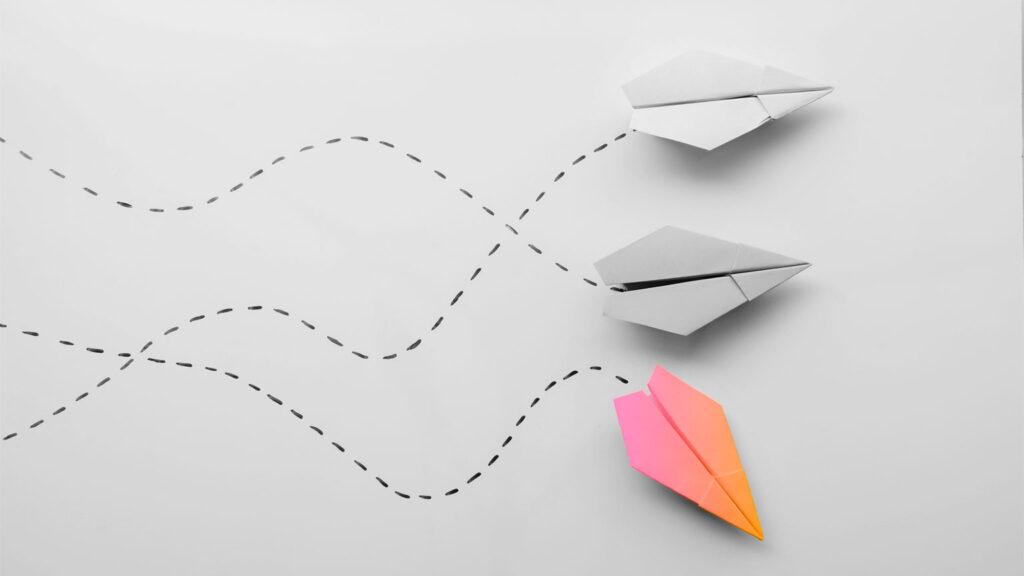 aeroplano di carta che cambia direzione rispetto agli altri due