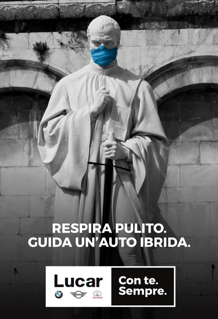 Affissione pubblicitaria di una statua lucchese con la mascherina anti smog.