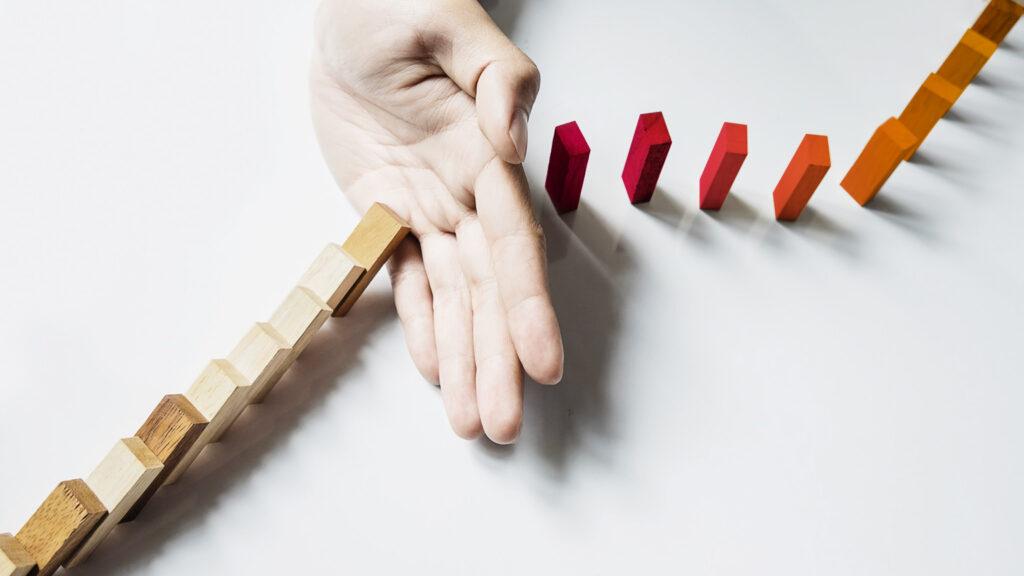 Mano che ferma un domino. Per rendere ogni evento un evento di successo sono necessarie grandi capacità di problem solving