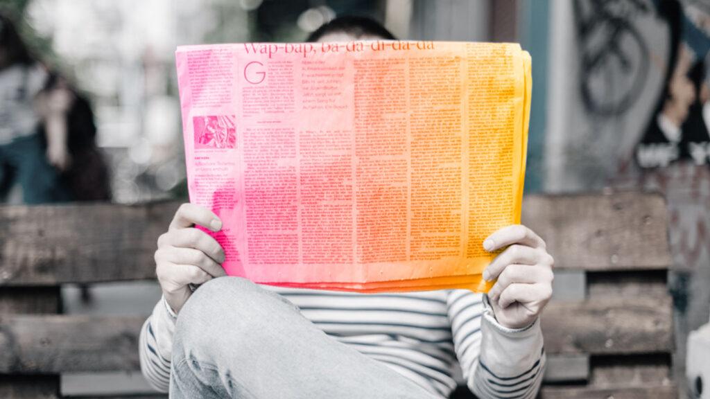 Uomo che legge un giornale su una panchina. Quando ad un rebranding non segue una strategia comunicativa a 360 gradi.